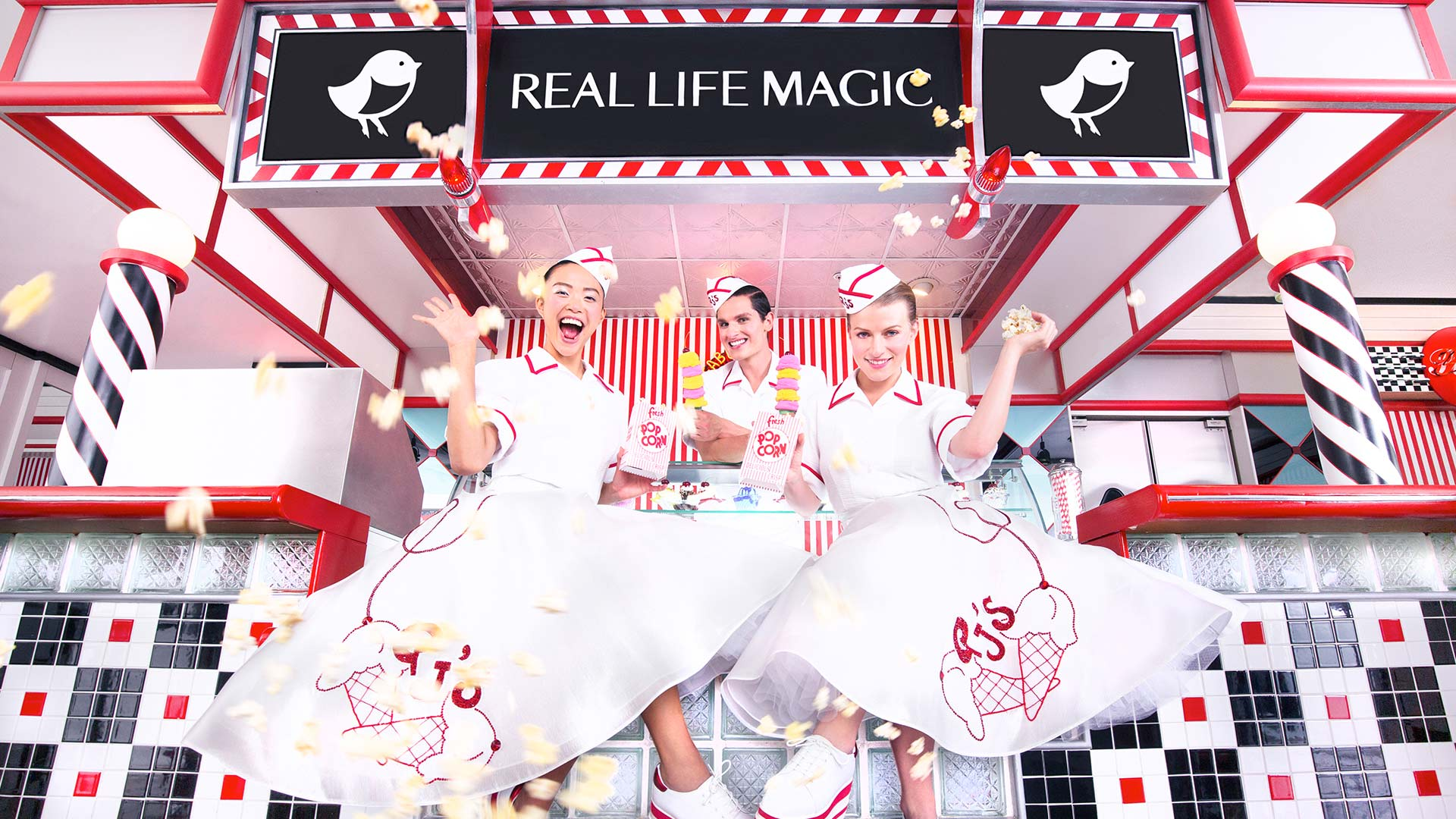 """""""Real Life Magic"""" sign above three girls in big skirts and hats serving ice cream"""