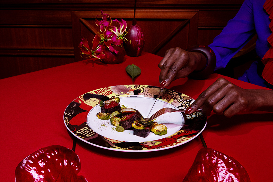 woman cutting food on a red table in a red room with red flowers