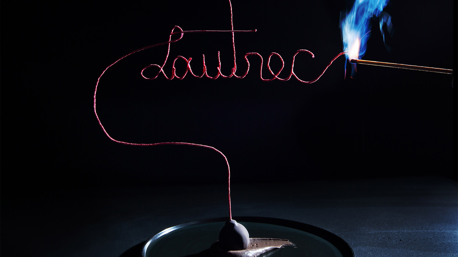 """fancy wick spelling """"Lautrec"""" in cursive being lit with a match"""