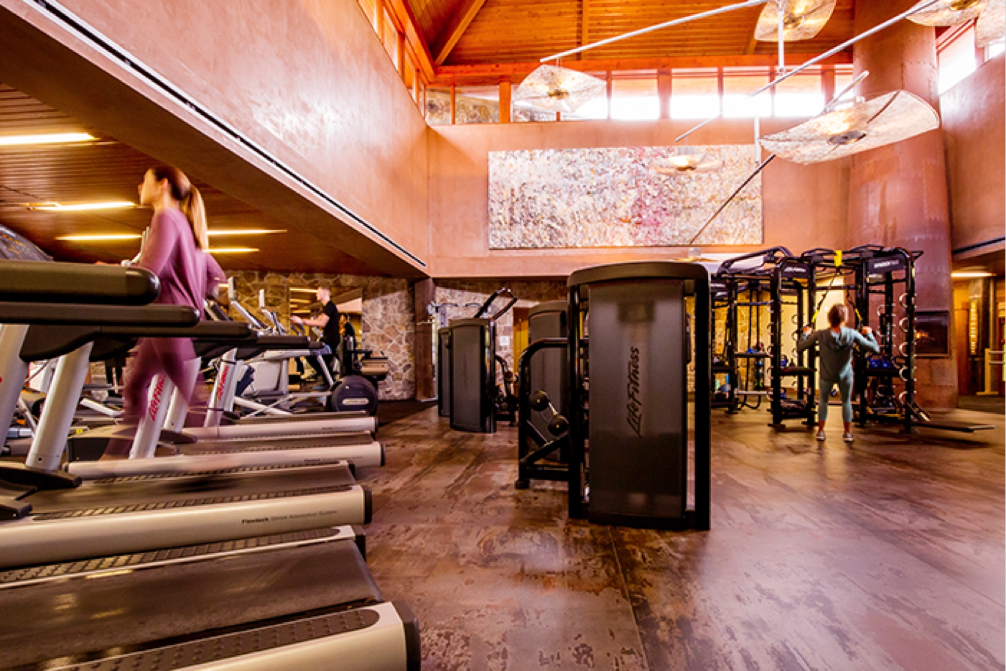 an action shot of a fitness center. There are treadmills lining the left side of the gym. There is a woman walking on one of the treadmills. There are weight machines on the right side of the room with a man using them