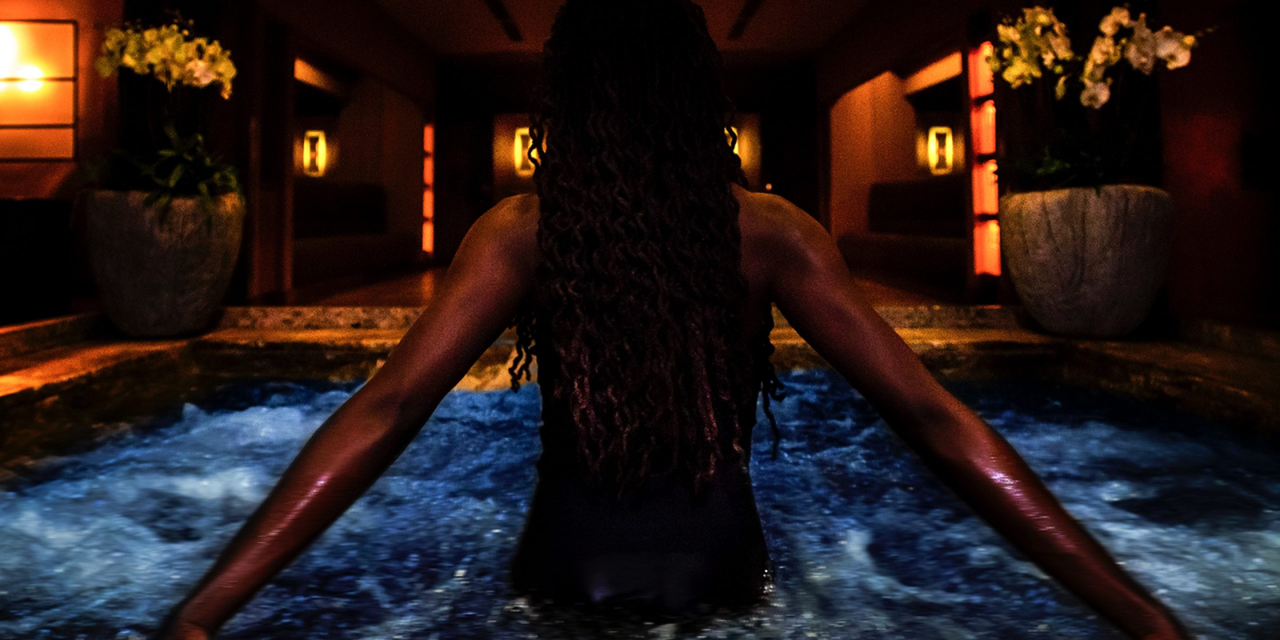 Woman's back emerging from a pool of water