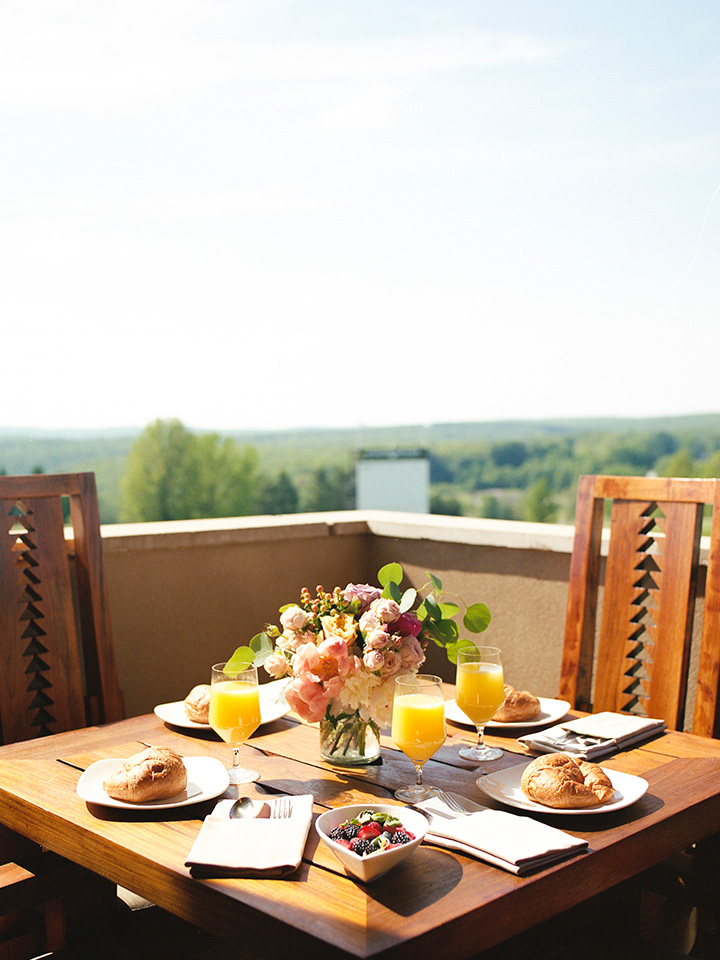 a detail shot of a table sitting on a balcony. There is an elegant brunch spread on the table and sweeping views of the resort grounds in the distance