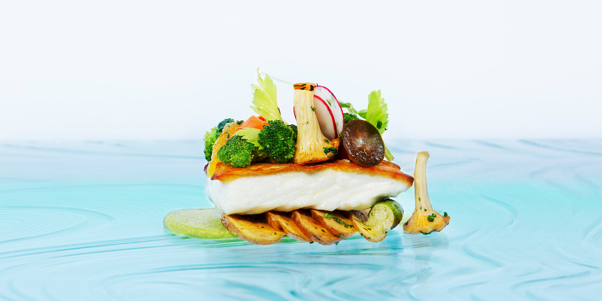 a detail shot of a piece of fish with seared vegetables topping it