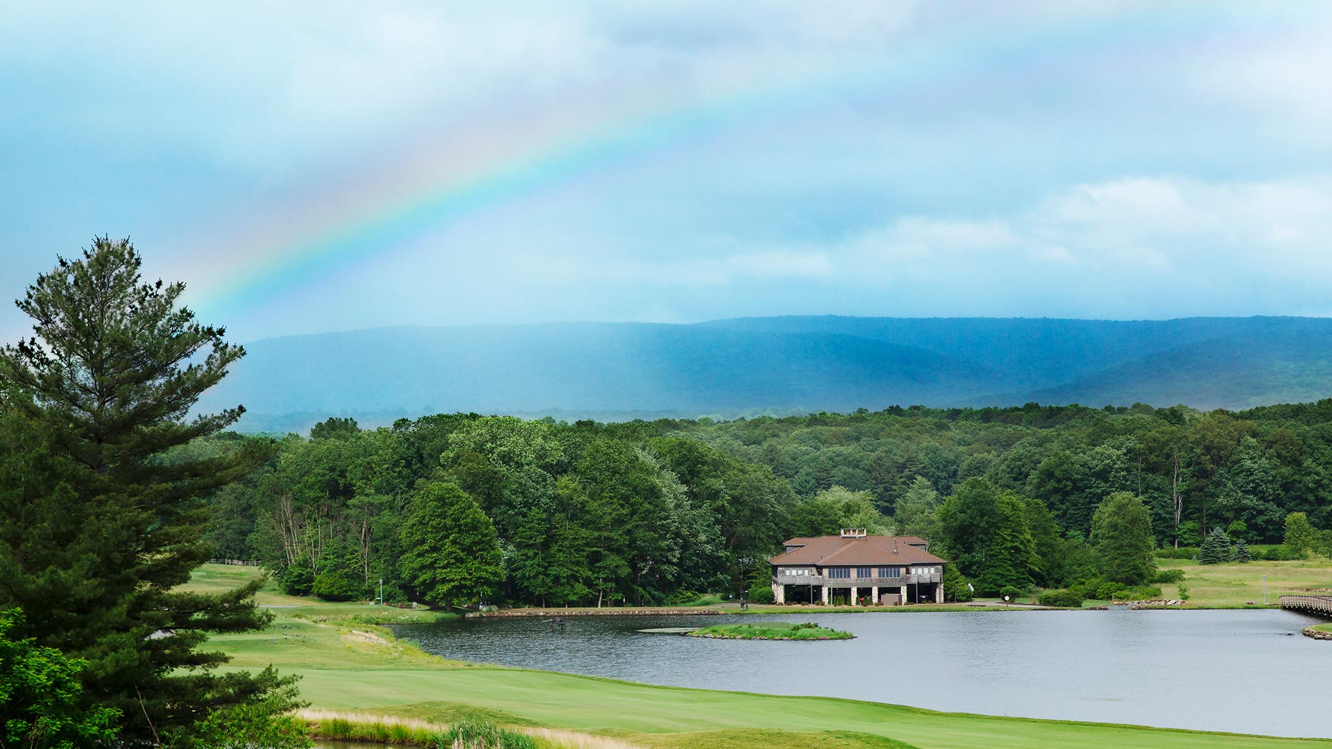a house is perched on the lake's edge and is surrounded by forests and the golf course. There is a rainbow across the sky