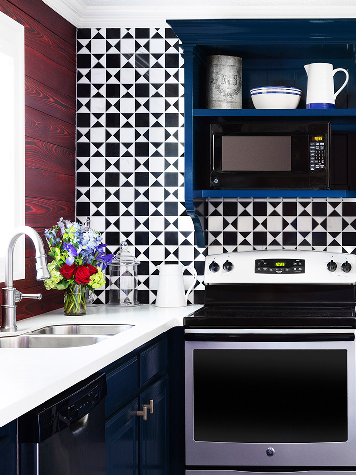 an interior shot of the full kitchen in the townhomes. The tiling is a geometric black and white print. There is a sink, a full fridge, an over and stovetop. There is ample counter and storage space.