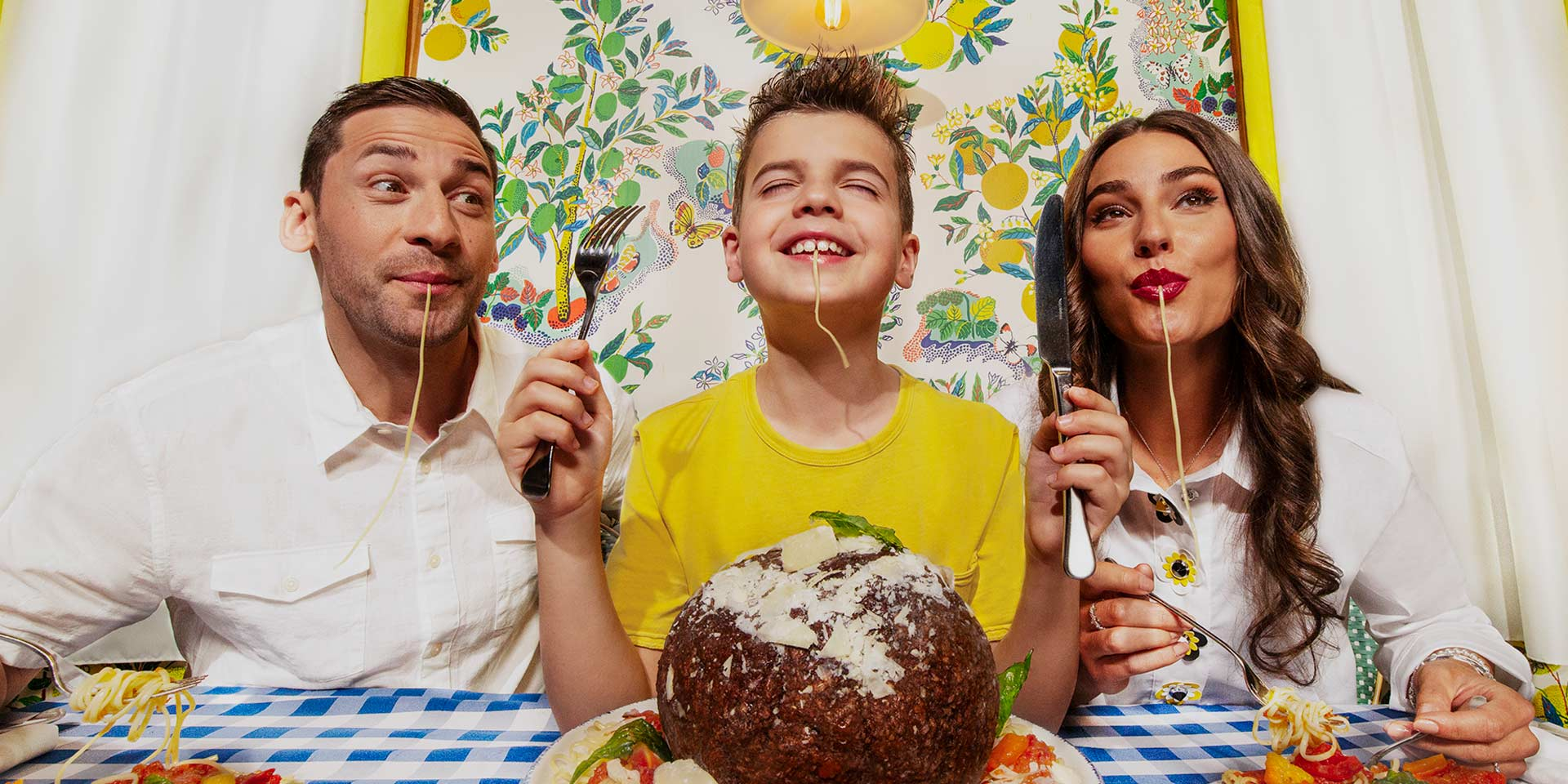 parents with their young son are slurping on spaghetti noodles and smiling