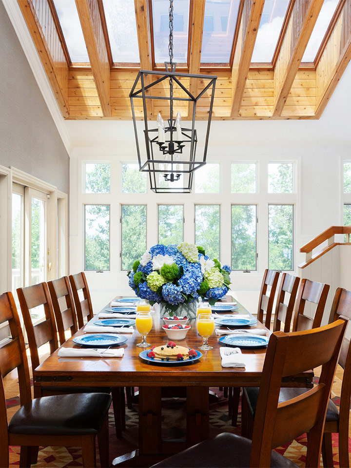 interior shot of the arden dining room. There is a long dark wood table with matching chairs. There are windows around the room and a large chandelier above the elegantly set table.