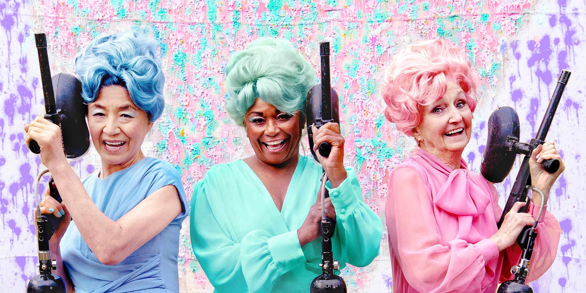 Three older women wearing monochrome outfits with wigs, one blue, one green, one pink, in front of a colorful backdrop