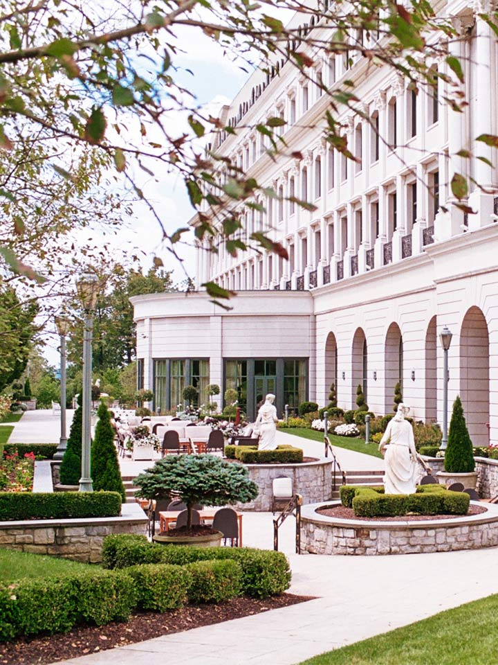 View of white building with a sculpture garden in front