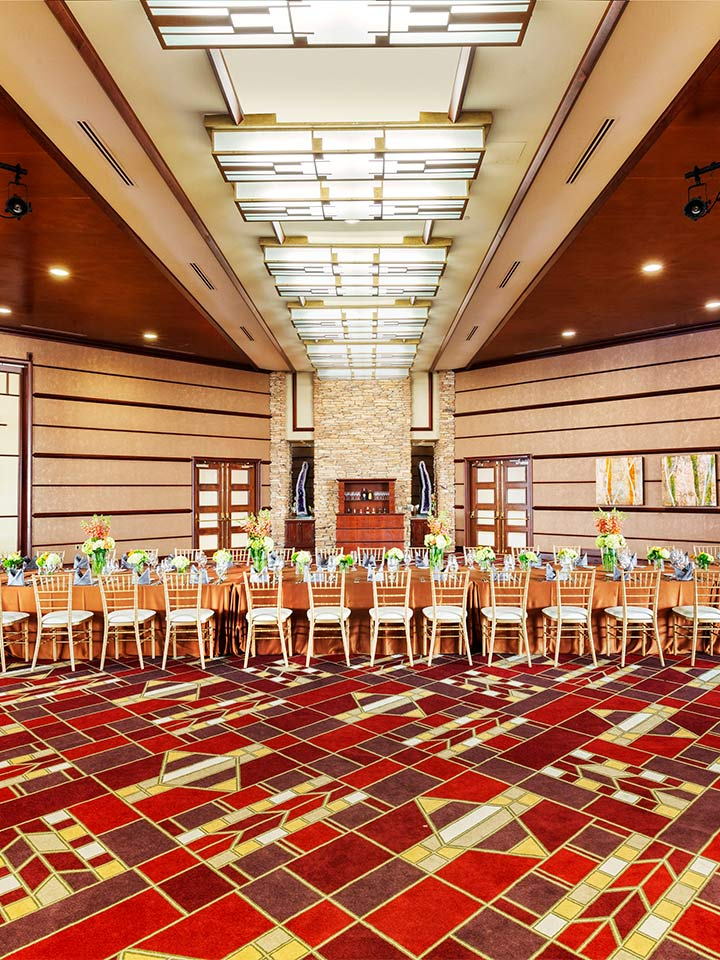 large room with red patterned carpet and tables with chairs