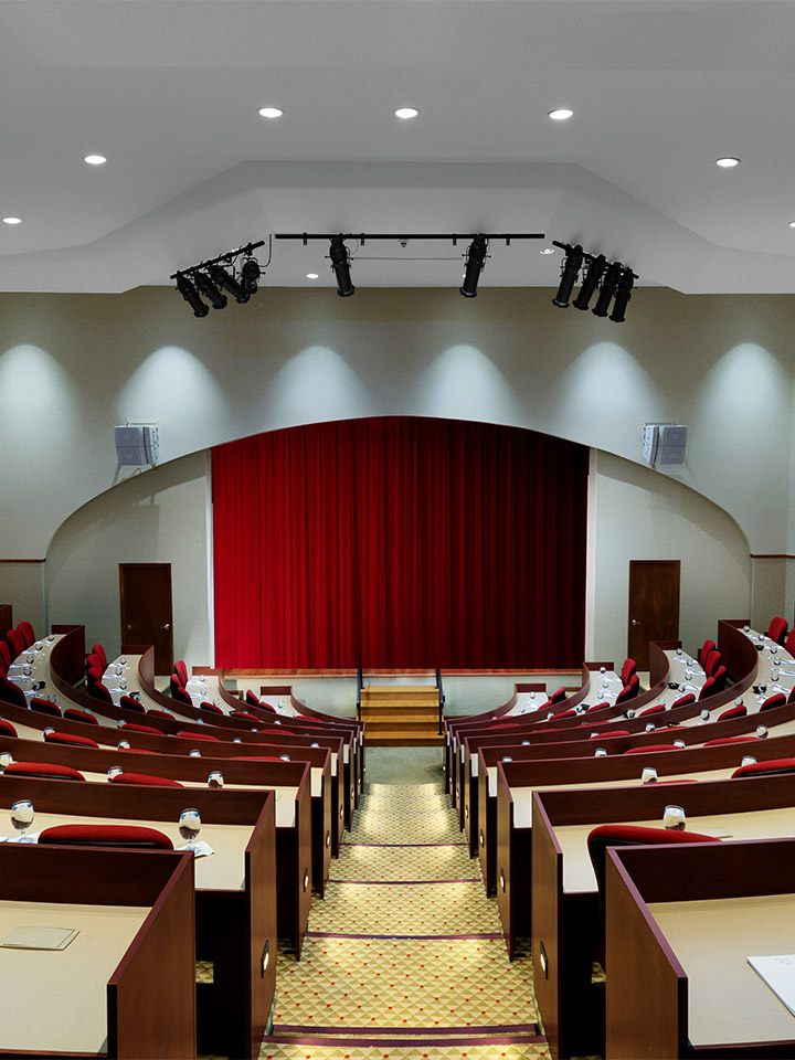 small auditorium with red curtain covering the stage