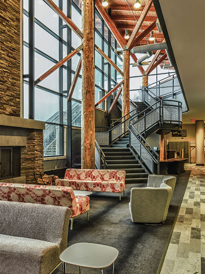 area with couches, wooden beams, a staircase, and a stone fireplace with big picture windows