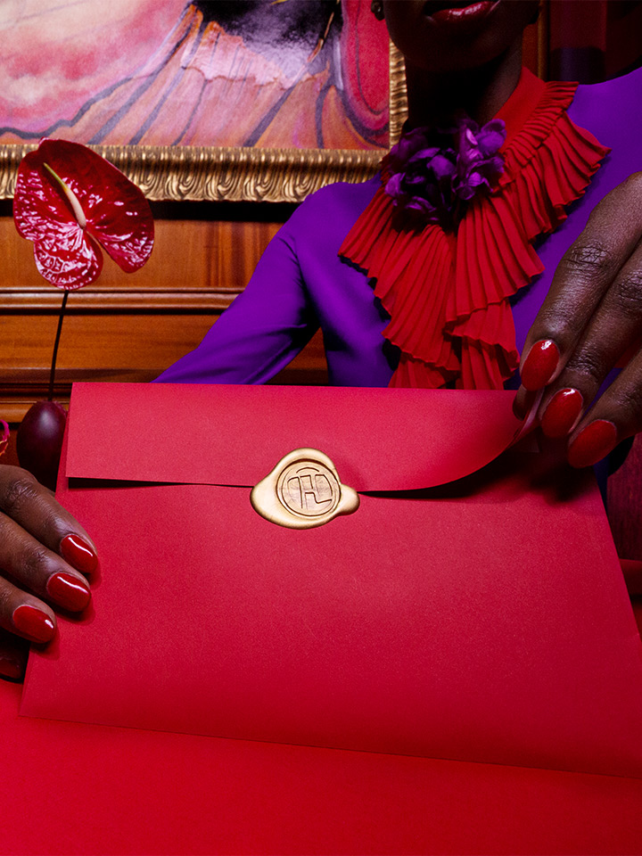 woman's hands holding a red envelope with gold seal