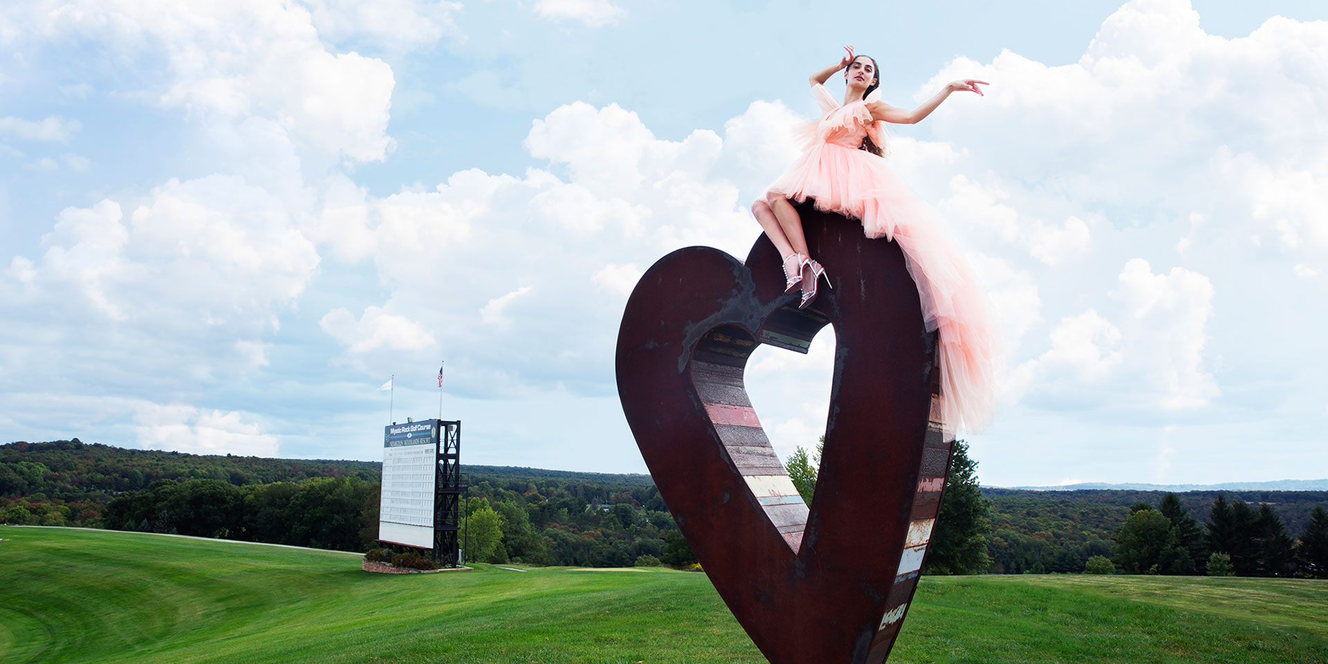 woman in a pink dress sitting on top of a heart sculpture outdoors