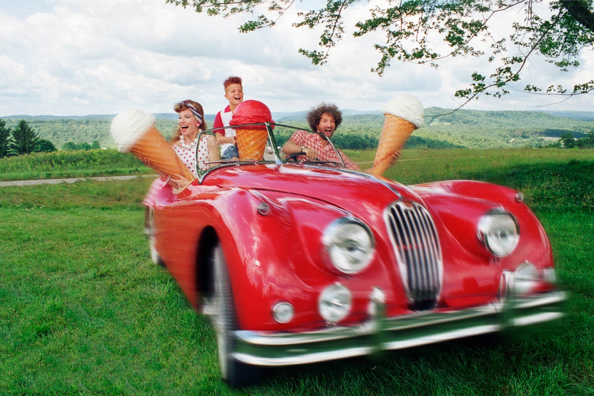 A family in a vintage red car in a field holding up giant ice cream cones