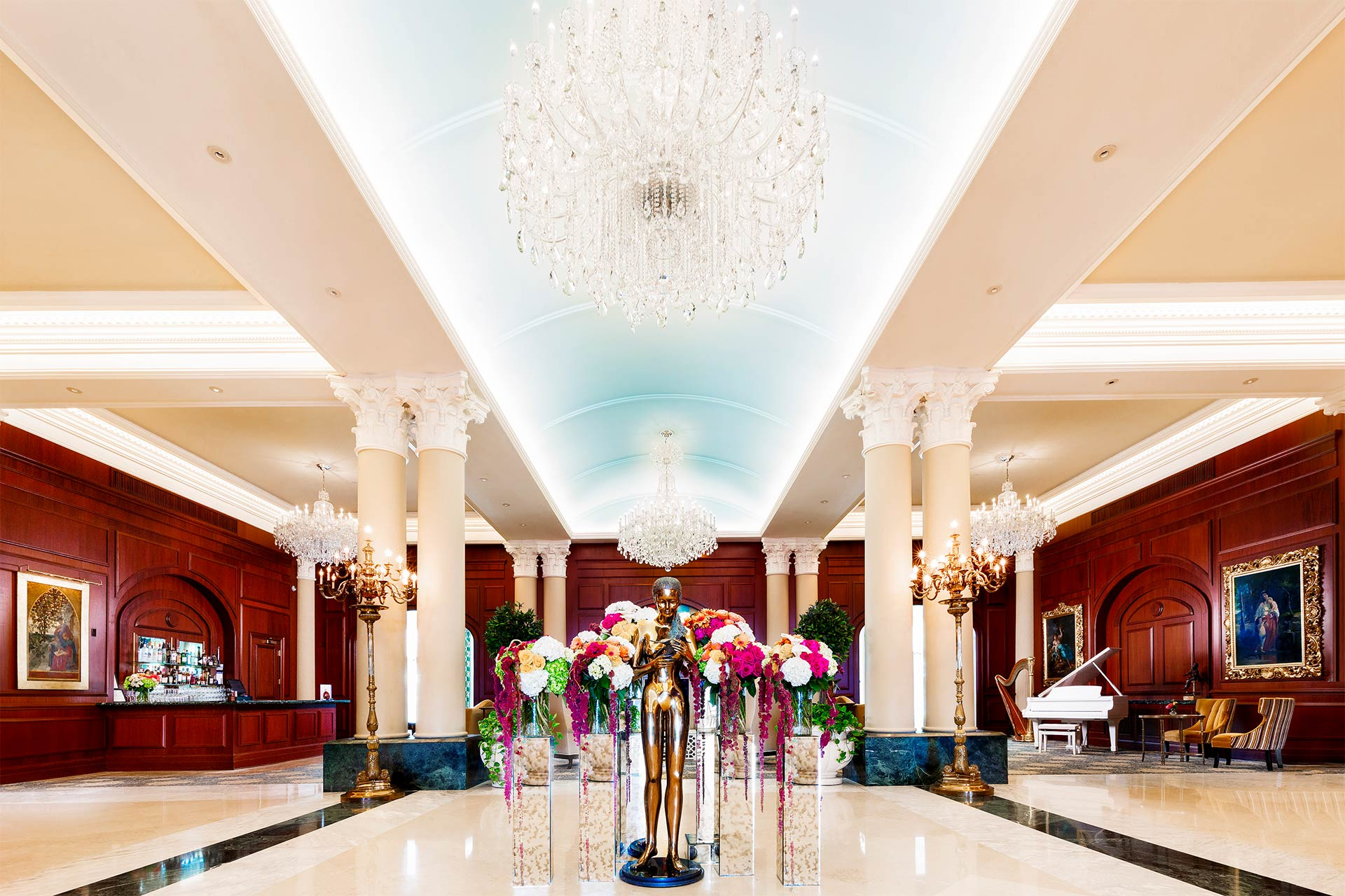 A fancy hotel lobby with a bronze statue of a woman in front and wooden walls and chandeliers above