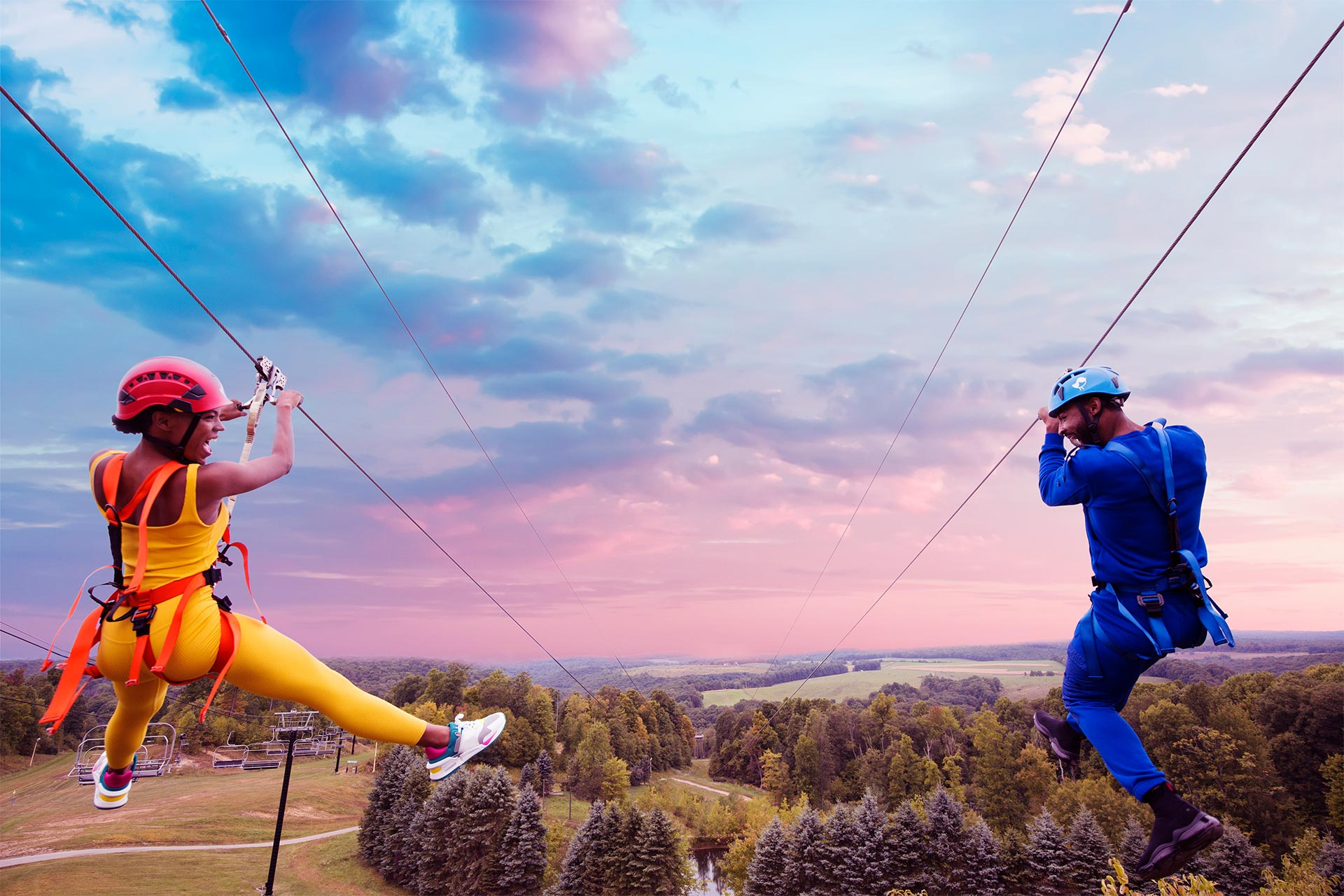 A man and a woman ziplining parallel to one another