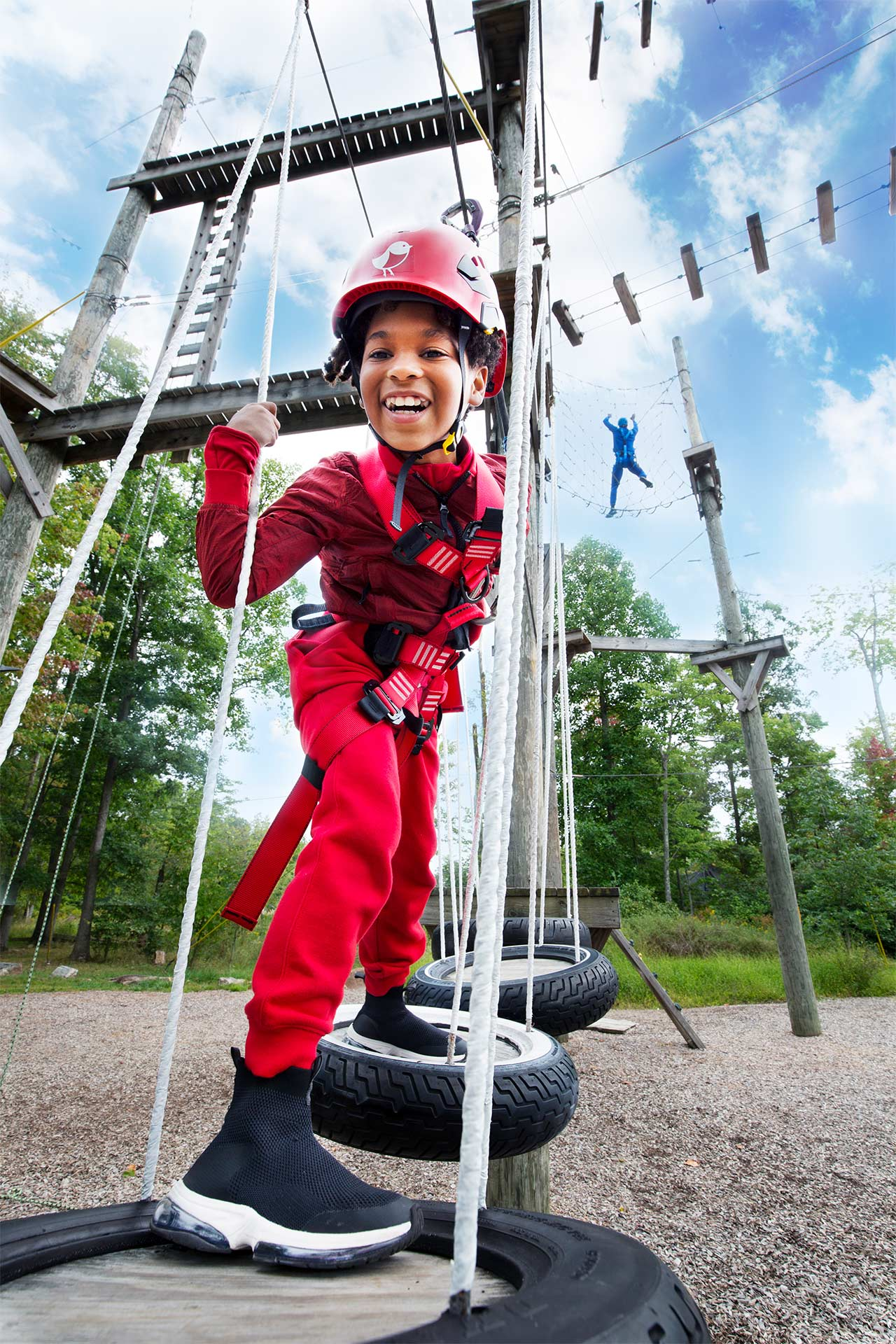 boy in red playing on a low ropes course