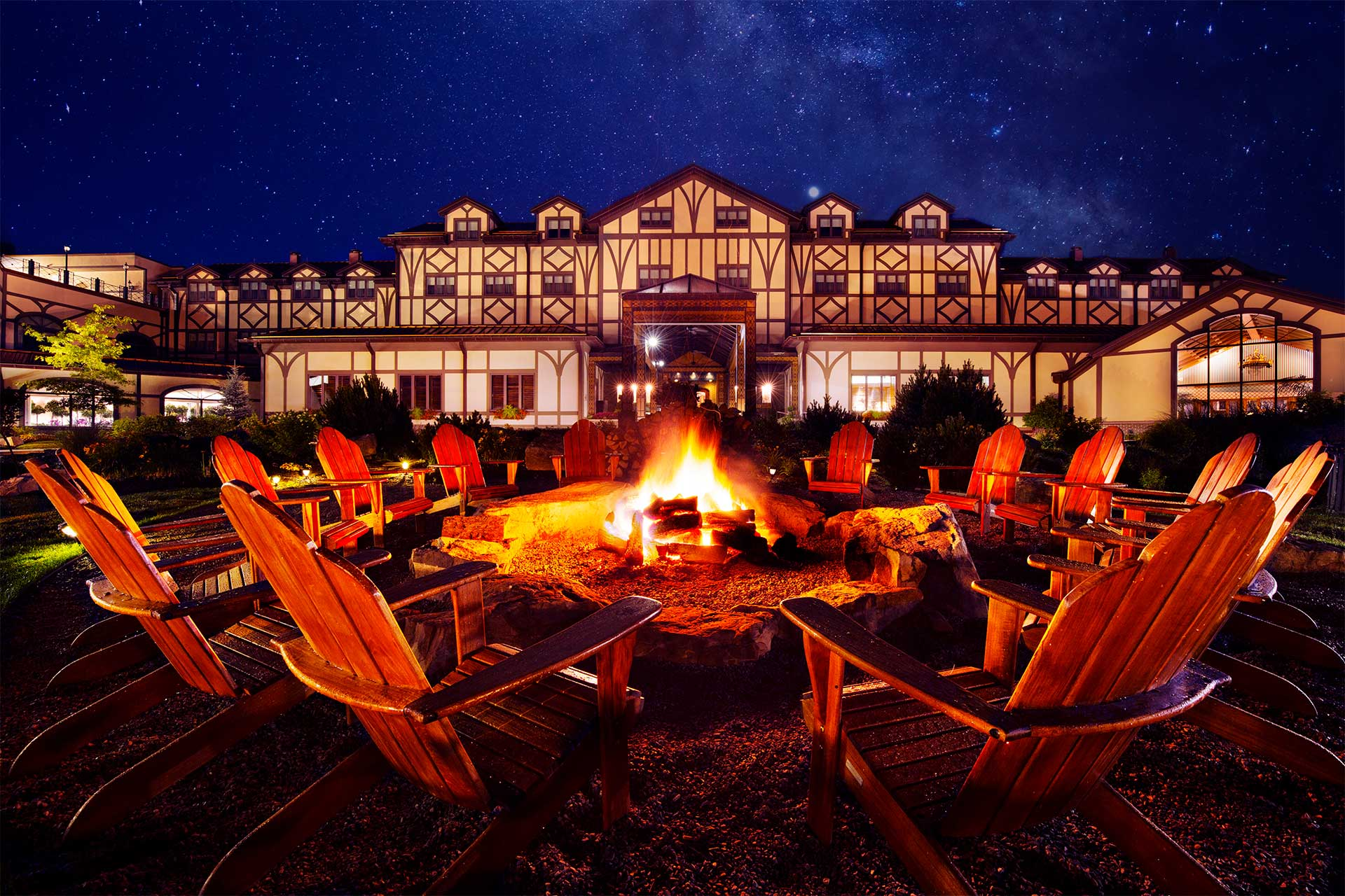 A large fire pit surrounded by chairs in front of a large lodge