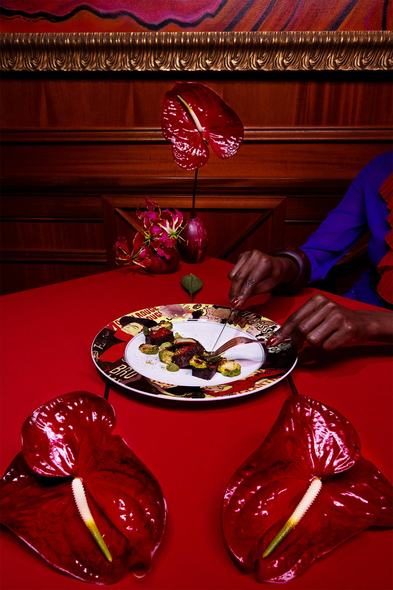 A woman cutting food on a red table in a red room with red flowers