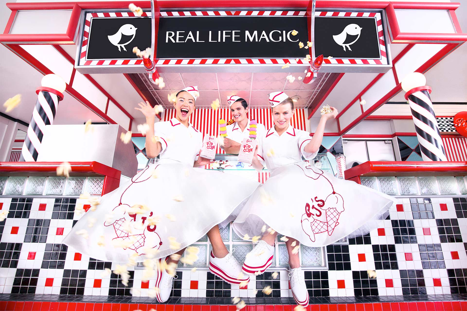 """Three women dressed in 60's style uniforms in front of an ice cream shop with a sign that says """"Real Life Magic"""""""