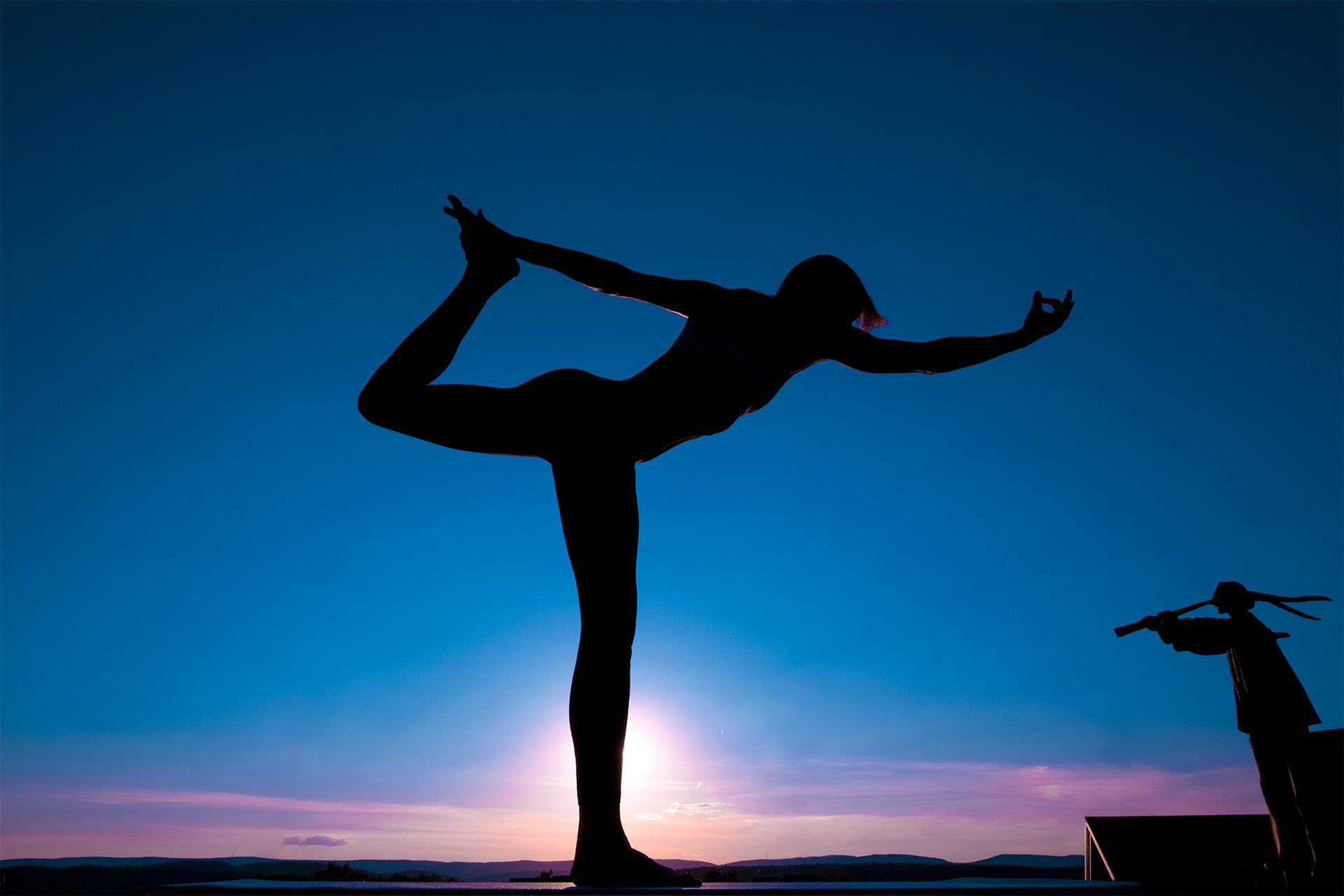 Silhouette of someone doing yoga at dusk