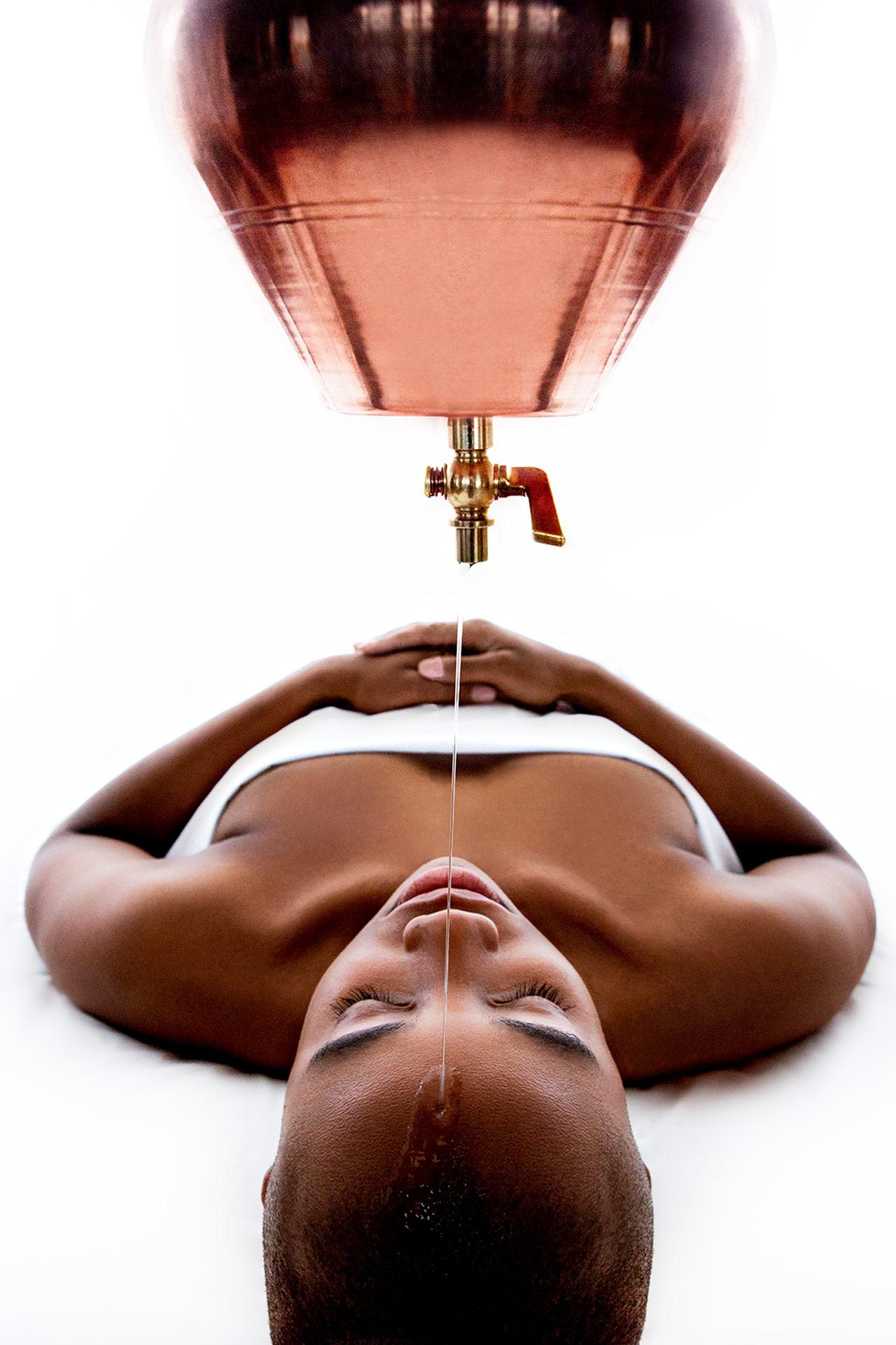 a woman getting a spa treatment where a liquid is dripped onto her head