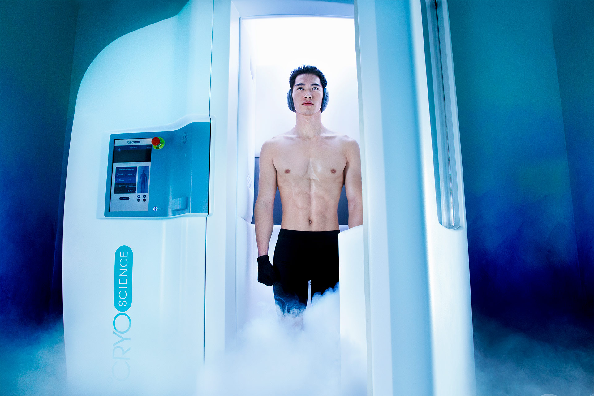 A shirtless man standing inside a white capsule with smoke surrounding
