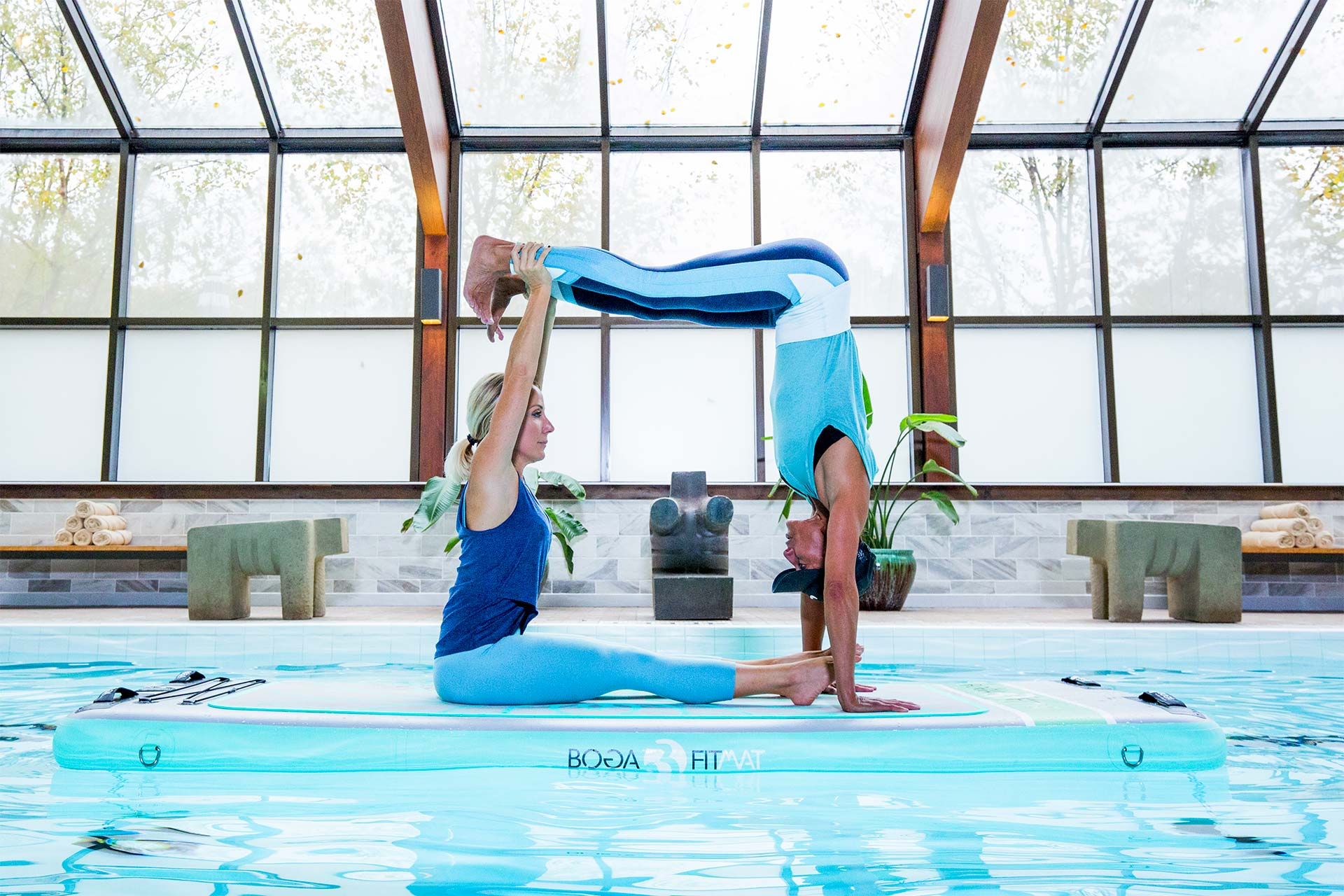 Two women creating a square with their bodies doing yoga on a float at an indoor pool