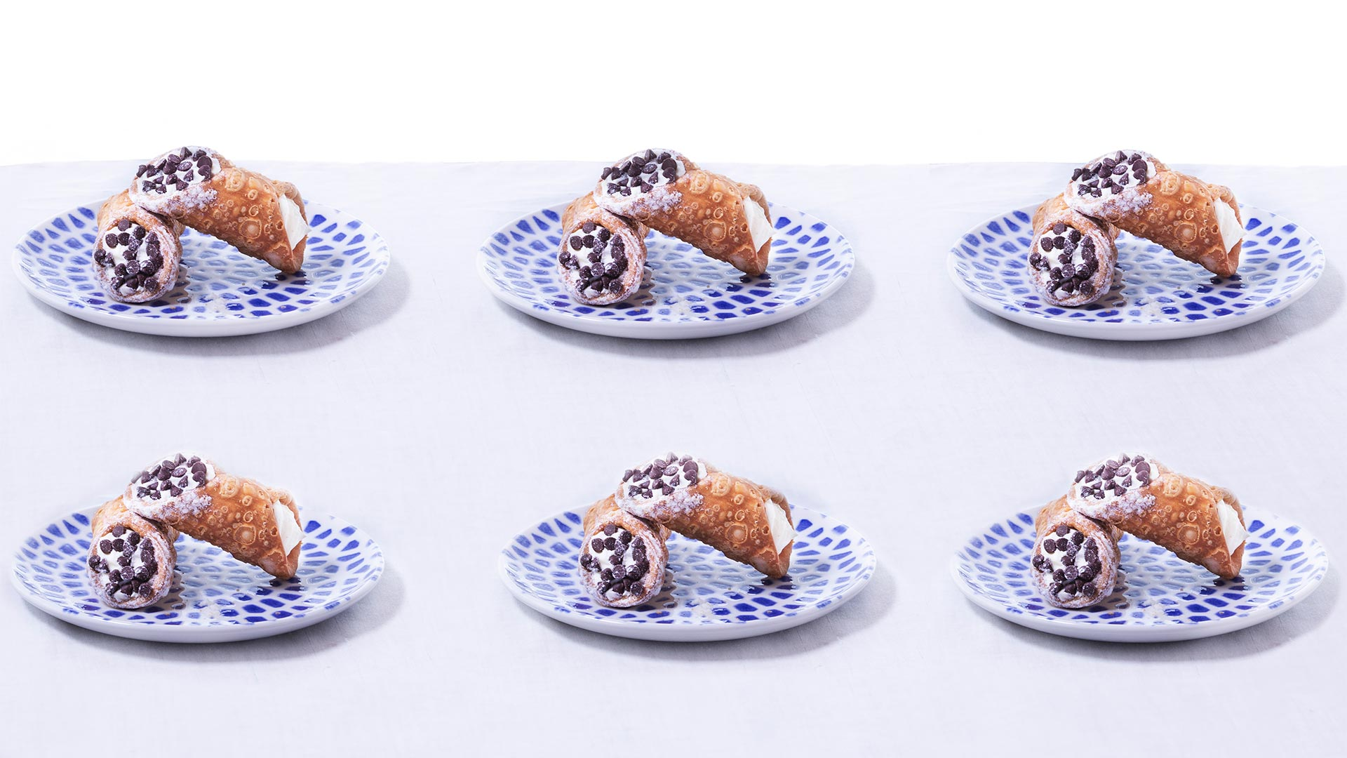 six cannolis on blue and white dotted plates