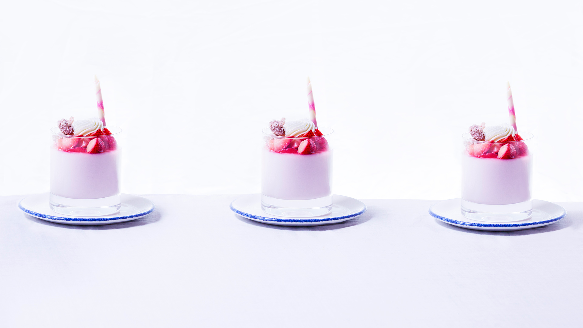 three pink strawberry desserts in a cup