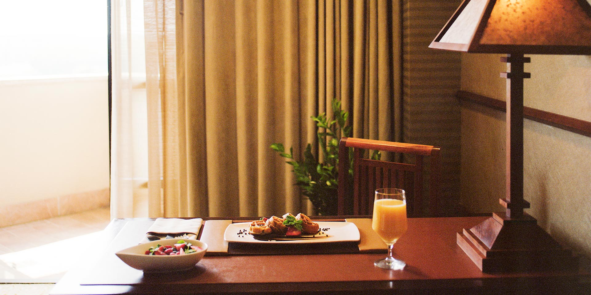 Waffles, orange juice, and a bowl of fruit is placed on a brown wooden table in a well light room.