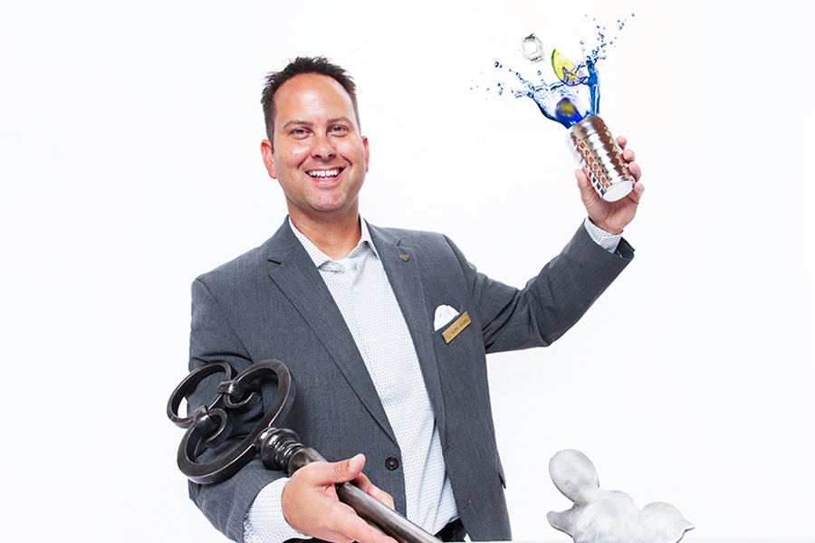 Smiling man throwing up a cup of blue liquid with lime in it and holding a giant key