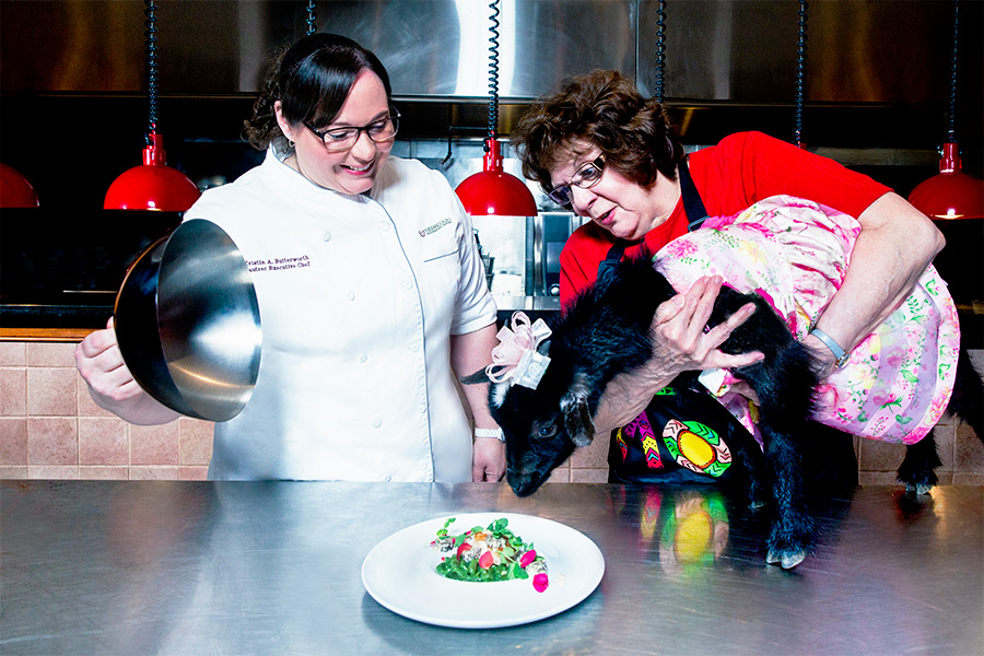 two women, one chef unvailing a plate of food and the other holding a black goat in a dress up to the plate