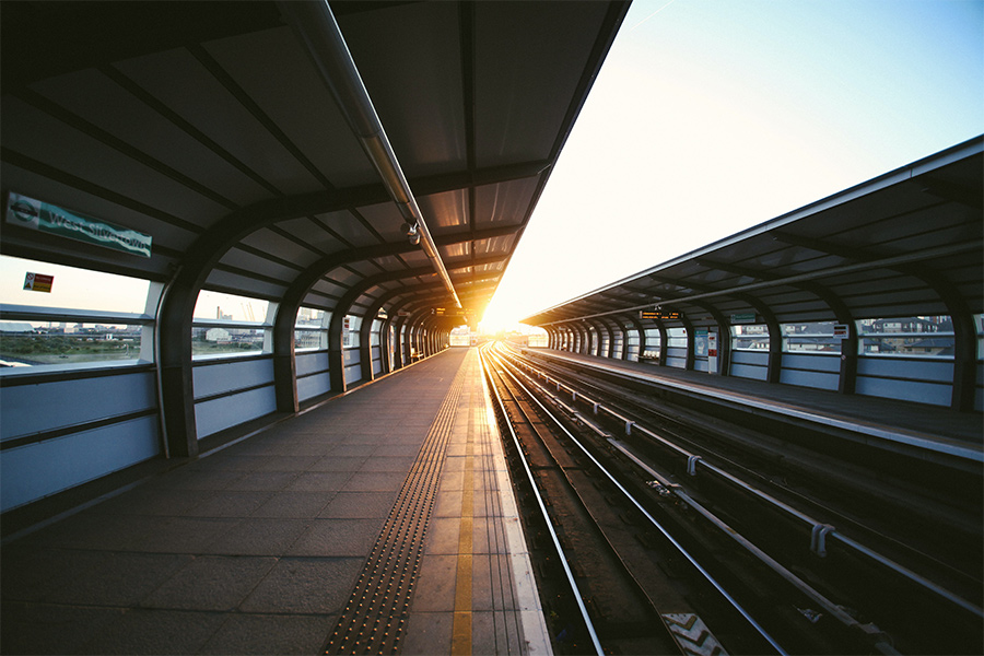 An empty train station platform with a beautiful sunset beaming from the middle.