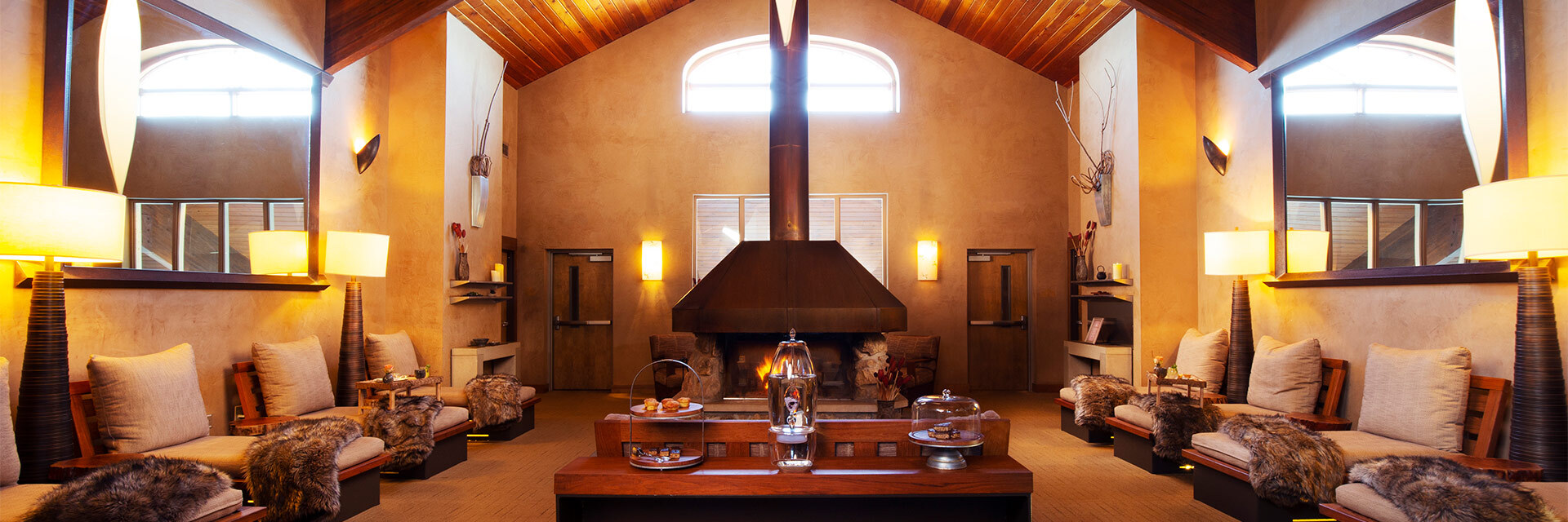 large room with seating on either side and a table in the middle and fireplace in the back, dimly lit