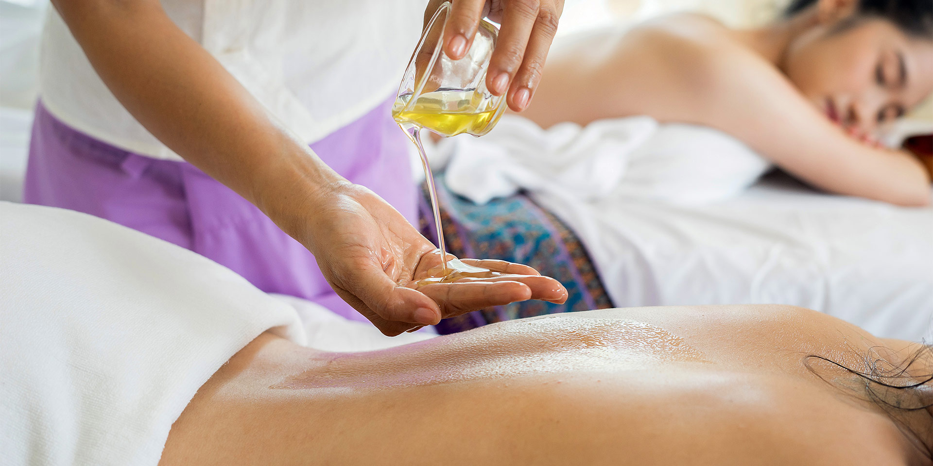 Massaging oil into a client's back.